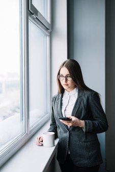 Young business woman using smartphone at window