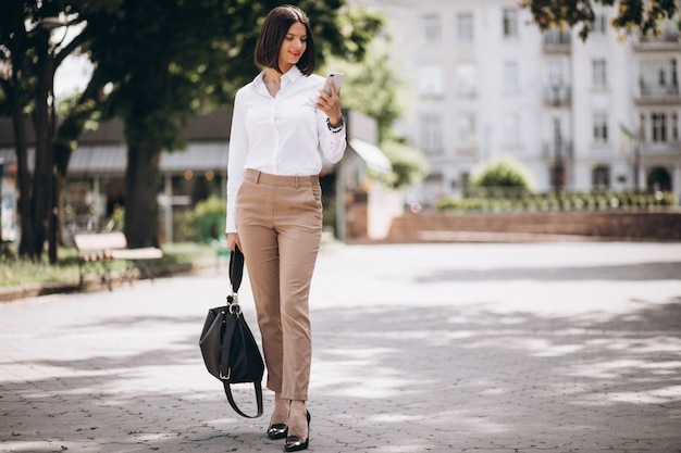 Young business woman walking in park