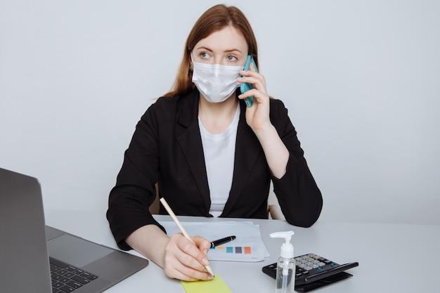직장 책상에 앉아 스마트 폰 이야기 얼굴 마스크를 쓰고 젊은 비즈니스 우먼