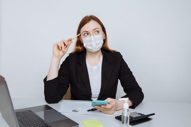 사무실 방에 직장 책상에 앉아 몇 가지 아이디어를 생각하는 얼굴 마스크를 착용하는 젊은 비즈니스 여자.