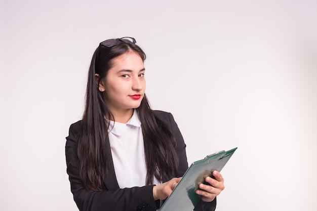 眼鏡をかけて、白い紙のフォルダーを保持している若いビジネス女性