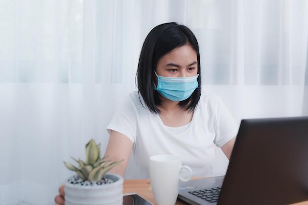 自宅で働くマスクを身に着けている若いビジネス女性