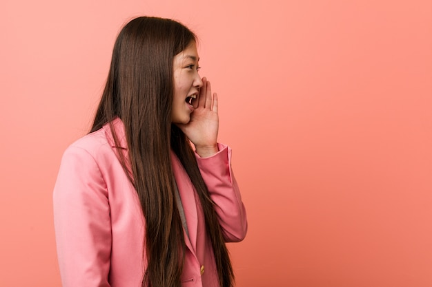 Young business woman wearing pink suit shouting and holding palm near opened mouth