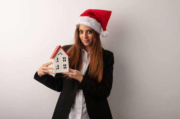 Young business woman wearing santa hat celebrating christmas day