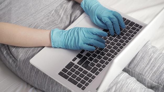 若いビジネスウーマンは、ホームオフィスの机に座っているラップトップコンピューターで作業する医療用フェイスマスク手袋を着用しています。コロナウイルスcovid19検疫の概念でリモートジョブを実行しているフリーランサー。クローズアップビュー