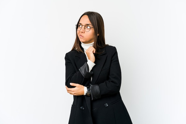 Young business woman on white wall confused, feels doubtful and unsure.