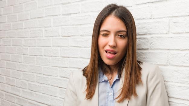 Молодая деловая женщина подмигивает, веселый, дружелюбный и беззаботный жест