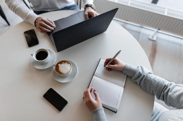 マネージャーと若いビジネスウーマンは、ラップトップでコーヒーを飲みながらテーブルのカフェに座って、ノートに書き込みます