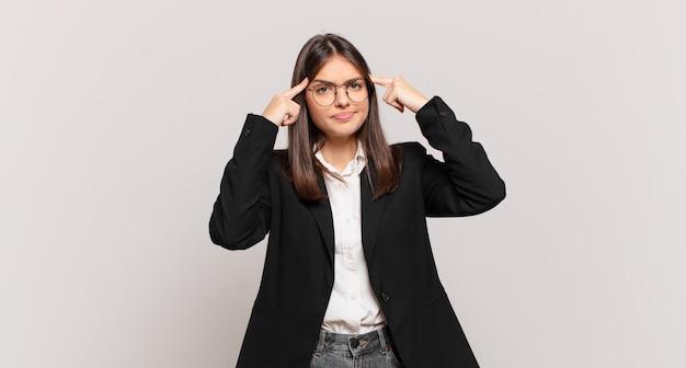 真面目で集中的な表情、ブレーンストーミング、挑戦的な問題について考えている若いビジネスウーマン