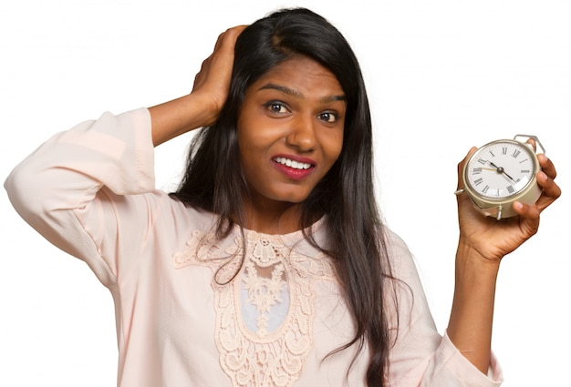 Young business woman with an alarm clock against white