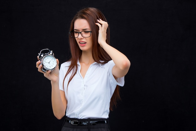 The young business woman with alarm clock