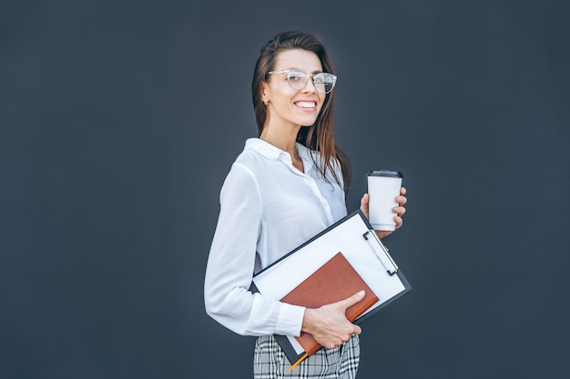 Young business woman with coffee and notebook on grey background.