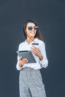 Young business woman with coffee and tablet on grey background.