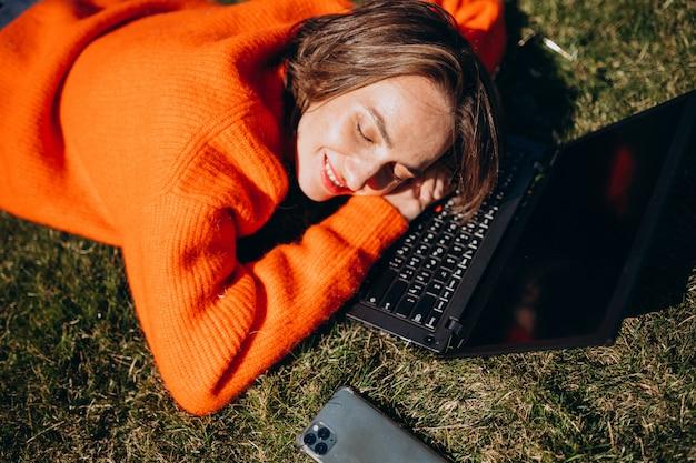 Молодая деловая женщина с ноутбуком на траве