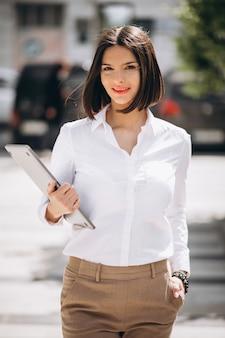 Молодая деловая женщина с ноутбуком на улице