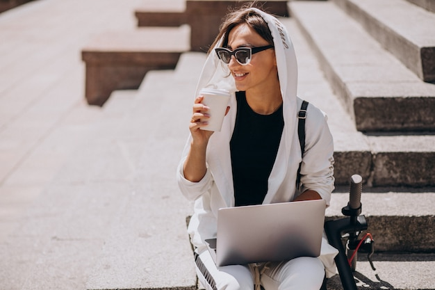 Young business woman with laptop sitting on stairs with scooter
