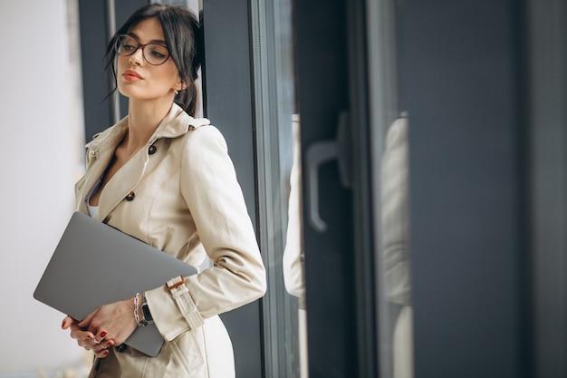 オフィスの窓のそばに立っているラップトップを持つ若いビジネス女性