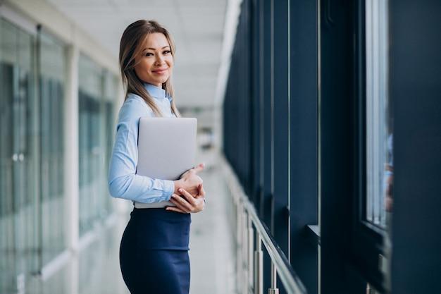 Молодая бизнес-леди с ноутбуком стоит в офисе