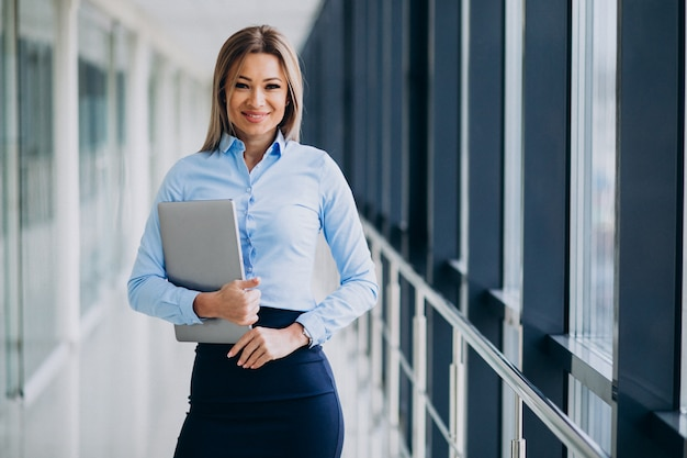 Young business woman with laptop standing in an office