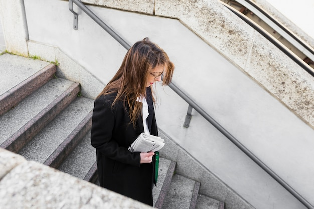 Young business woman with newspaper walking down stairs