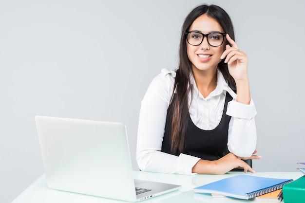 白で隔離のオフィスでノートブックを持つ若いビジネス女性