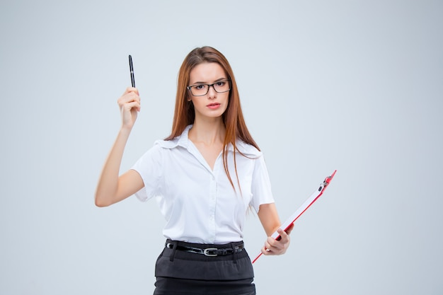 The young business woman with pen and tablet for notes on gray wall