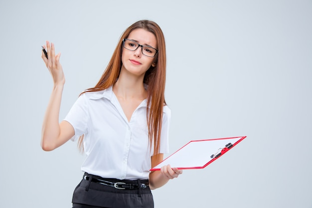 The young business woman with pen and tablet for notes on gray