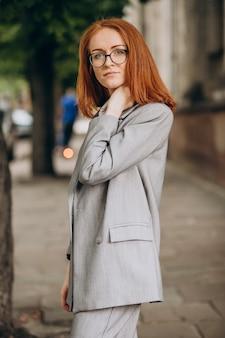 Молодая деловая женщина с рыжими волосами на открытом воздухе
