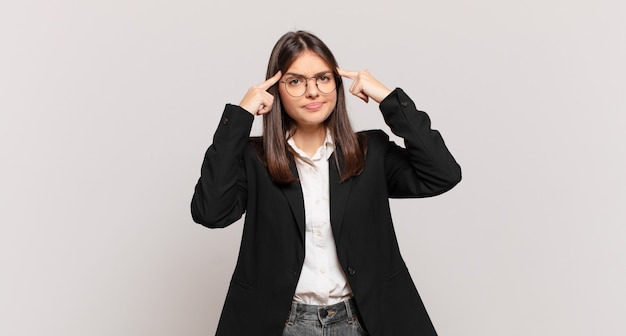 Young business woman with a serious and concentrated look, brainstorming and thinking about a challenging problem