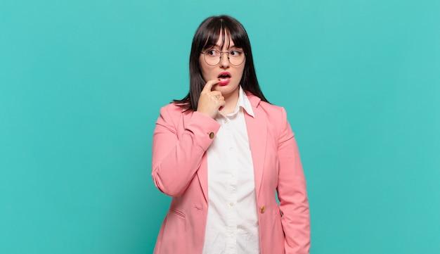 Молодая деловая женщина с удивленным, нервным, встревоженным или испуганным взглядом, смотрящая в сторону в сторону копии пространства