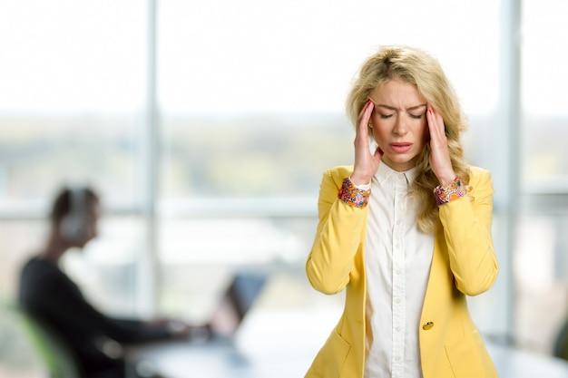 Молодая бизнес-леди с ужасной головной болью. подавленный молодой менеджер трогает ее скулу и держит глаза закрытыми, стоя у окна офиса.