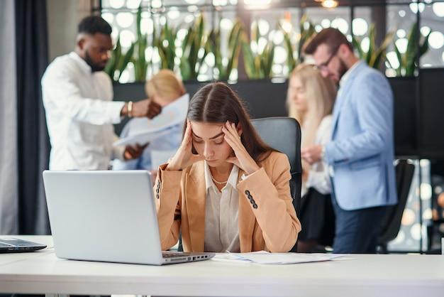 ハードな仕事の後に疲れて頭痛に苦しんでいるラップトップの前のオフィスのテーブルで働く若いビジネス女性。