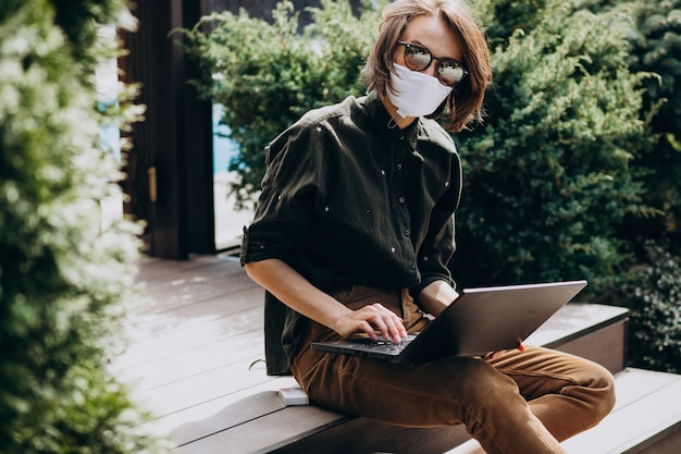 Young business woman working on computer from home in mask