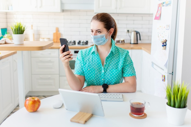 Young business woman working from home by the light table in the kitchen with tab, wearing protective mask.