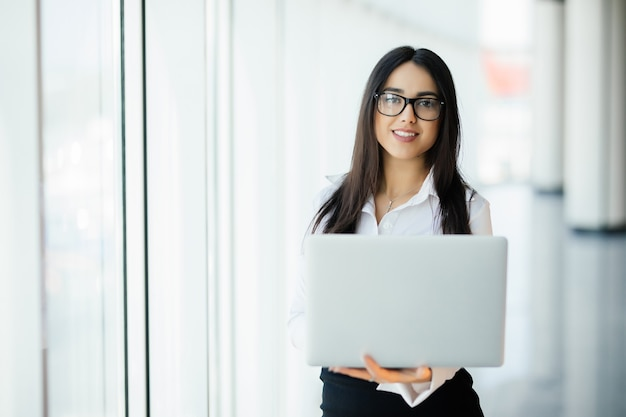 Young business woman working in her luxurious office holding a laptop standing against panoramic window with a view on business district
