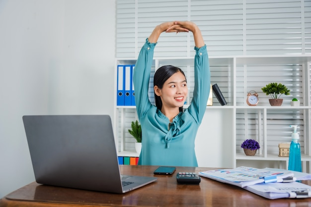 Young business woman working at home raise up her hands over head to relax from hard working, coronavirus.