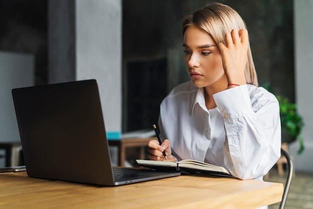 Молодая деловая женщина работает дома, сидит перед ноутбуком и думает
