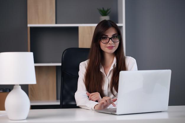 노트북을 사용 하여 그녀의 사무실에서 일하는 젊은 비즈니스 우먼