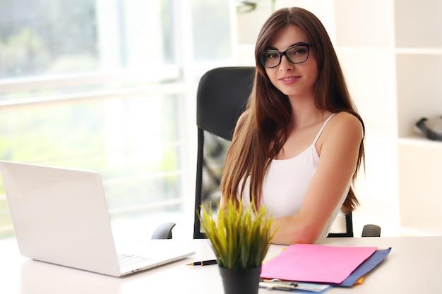 랩톱을 사용하는 그녀의 사무실에서 일하는 젊은 비즈니스 여자.