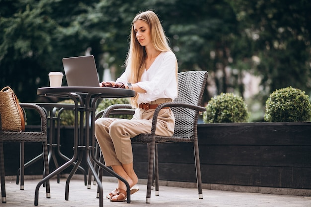 Young business woman working on laptop outside in a cafe
