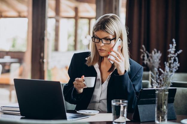カフェ内のコンピューターに取り組んでいる若いビジネス女性
