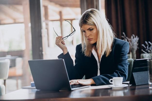 Молодая деловая женщина, работающая на компьютере в кафе