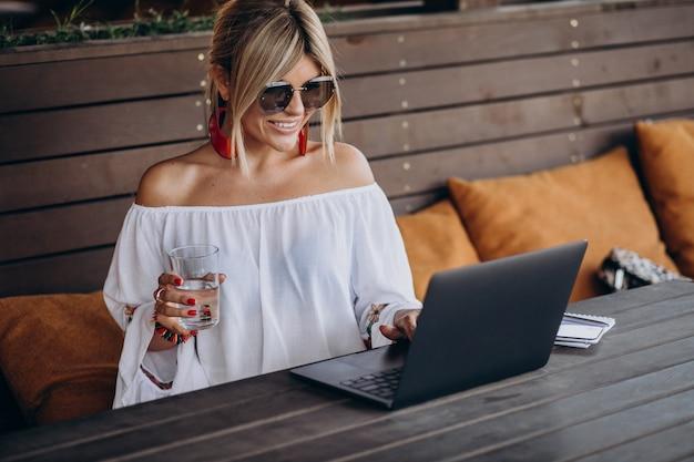 Молодая деловая женщина, работающая на компьютере в баре