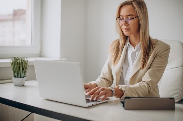 Молодая деловая женщина, работающая на компьютере в офисе