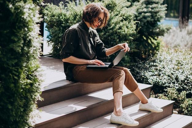 自宅のラップトップに取り組んでいる若いビジネス女性