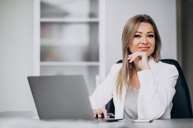 Молодая бизнес-леди работая на компьтер-книжке в офисе