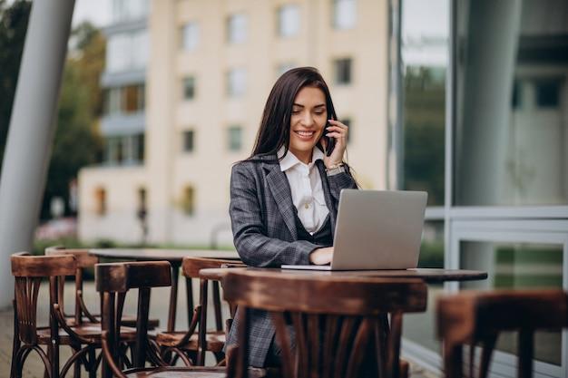 ラップトップに取り組んでいる若いビジネス女性