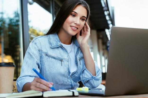 젊은 비즈니스 여자 집에서 오픈 테라스에서 일하고, 노트북 앞에 앉아, 그녀의 손에 스마트 폰을 들고.