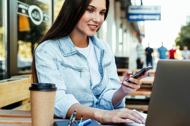 Молодая деловая женщина, работающая на открытой террасе дома, сидя перед ноутбуком, держа смартфон в руке.