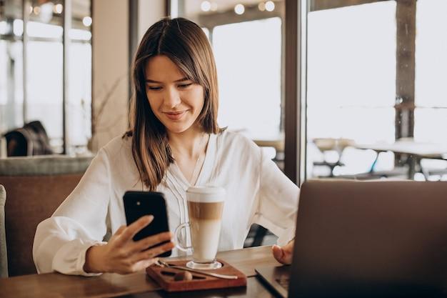 カフェでオンラインで働いてコーヒーを飲む若いビジネスウーマン